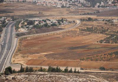 道路沿いに壁がある。パレスチナ人の土地が道路で囲まれ孤立している。